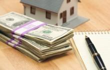 Деньги, игрушечный домик и блокнот