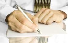 Мужчина пишет на листке