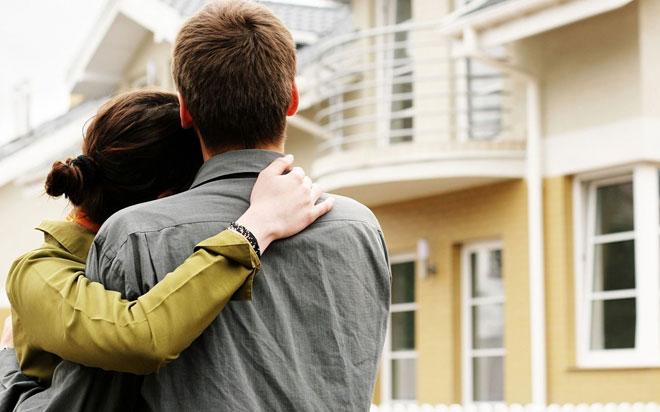 Молодая пара смотрят на дом