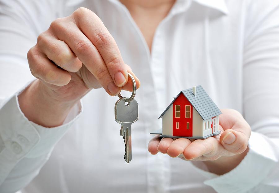 Макет дома и ключи в руке