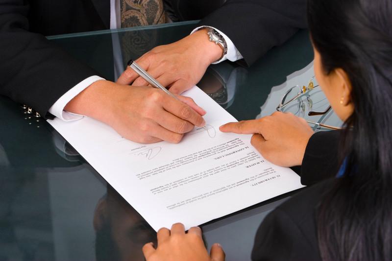 Мужчина и женщина подписывают документ