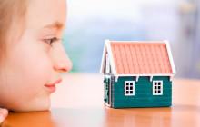 Девочка смотрит на макет дома