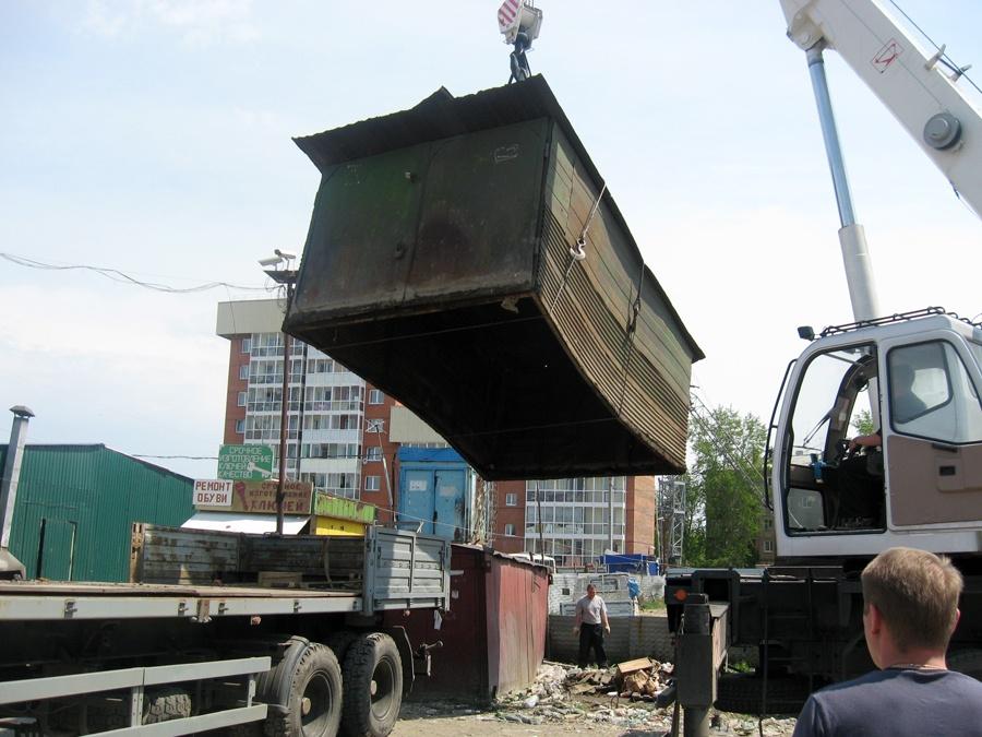 Автокран грузит металлический гараж на трейлер