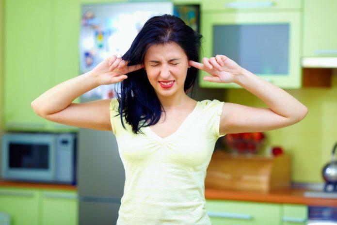 Женщина закрывает уши