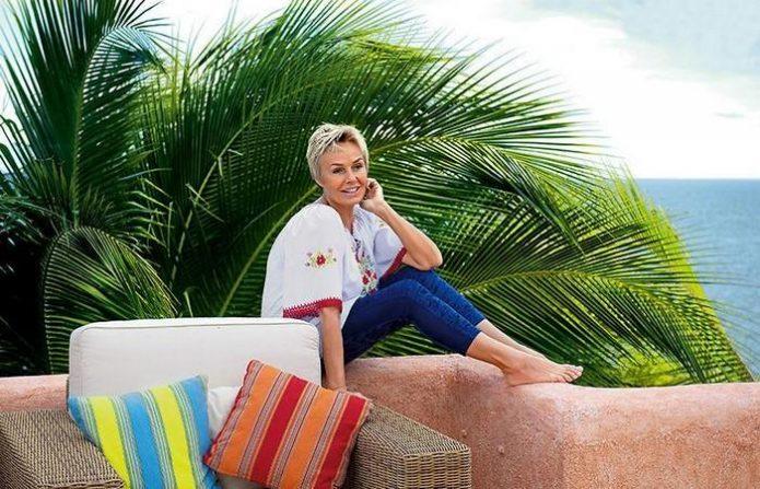 Наталья Андрейченко сидит во дворе виллы с видом на море