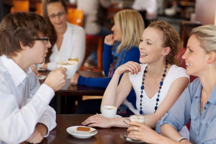 Молодые люди беседуют за столиком в кафе