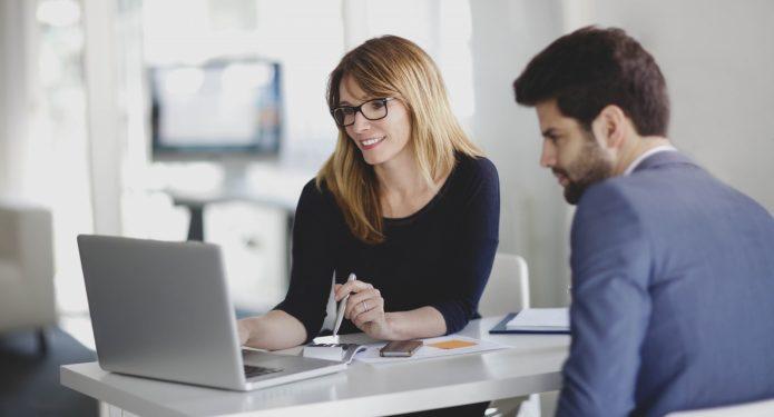 Женщина и мужчина смотрят на экран ноутбука