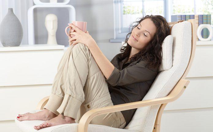 Девушка с чашкой в кресле